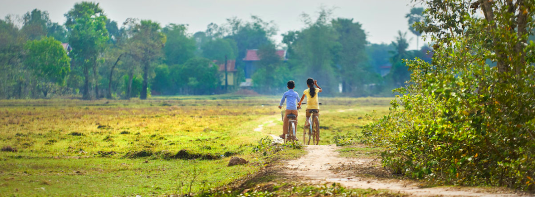 Two children on bicycles on an unpaved road in green field