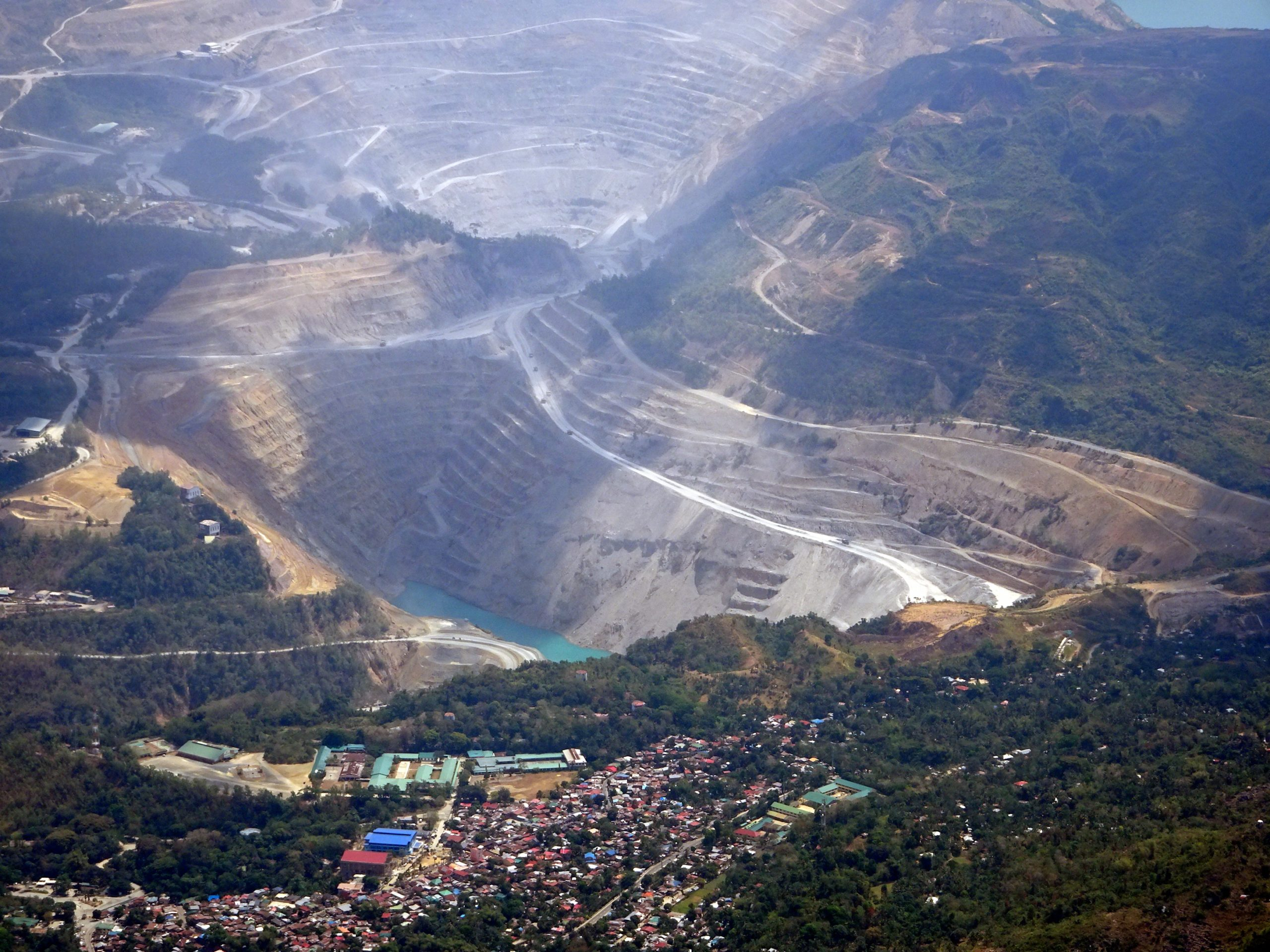Banner image of the Carmen Pit, an open-pit copper mine site in Toledo, Cebu in the central Philippines, image taken in April 2016. Image by P199 via Wikimedia Commons (CC BY-SA 4.0)