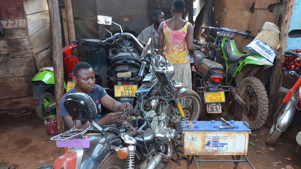 A mechanic repairs a motorcycle in one of the garages on Obote Way in Jinja City on Monday. PHOTO/TAUSI NAKATO