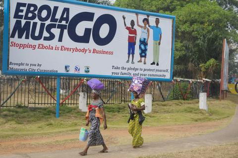 "Two women walk in front of a billboard, which says ""Ebola must go. Stopping Ebola is Everybody's Business"" in Monrovia, Liberia."