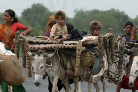 Tribal people walk with their belongings in Tarapur village, about 87 km (54 miles) south from the western Indian city of Ahmedabad July 13, 2007. REUTERS/Amit Dave (INDIA)