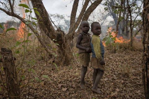 Two of Julius Peter's children stand in front of a fire their father lit to clear land for farming. Photo taken in Lulung village, Lologi on February 25, 2018. Sally Hayden/Thomson Reuters Foundation