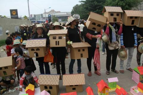 Protesters carry cardboard cutouts of houses during a march to mark World Habitat Day in Phnom Penh, Oct. 5, 2015.