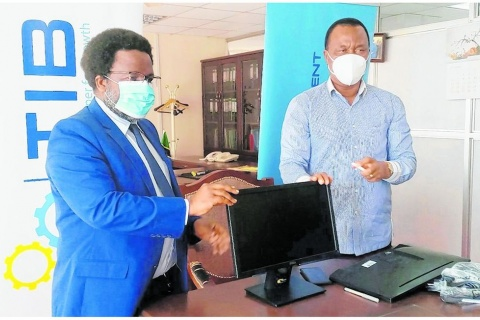 Land, Housing and Human Settlements Development minister William Lukuvi (right) receives computers donated by the TIB Development Bank