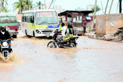 Motorcycle riders and commuter buses cross at the flooded section of Kigogo Road in Dar es Salaam following the heavy rainfall that pounded the city recently. PHOTO   MICHAEL MATEMANGA