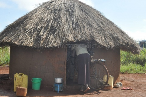 Opondo entering with a bicycle in her muddy thatched house.
