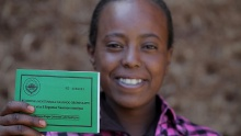 Asilya Gemmal displays her land certificate, given by the Ethiopian government, with USAID assistance.