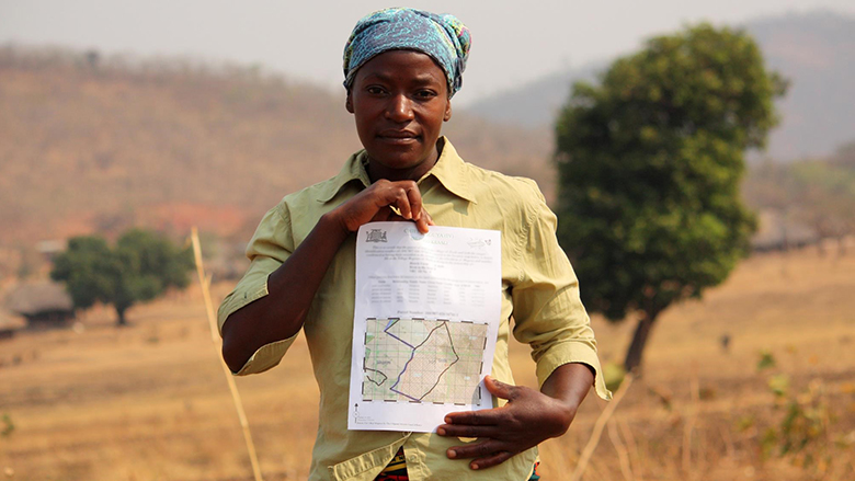 A woman holding her land certificate in rural Zambia. © Jeremy Green